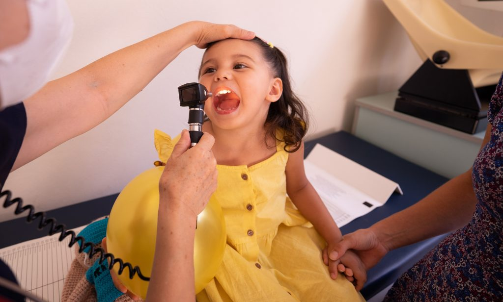 Photo of a little girl smiling while a doctor checks her throat with a lighted scope. Photo by Los Muertos Crew on Pexels.