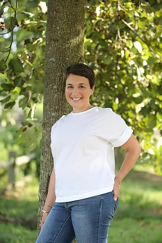 Photo of doctor Michelle Neier, in casual clothing, posed in front of a tree