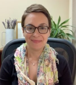 Photo of Dr Michelle Neier, a woman with short brown hair and brown tortoise glasses in a pink scarf, sitting in an office chair.